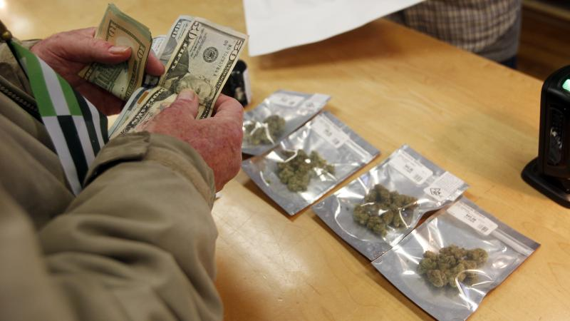 A customer buys marijuana at Harborside dispensary in Oakland, Calif., on Monday.