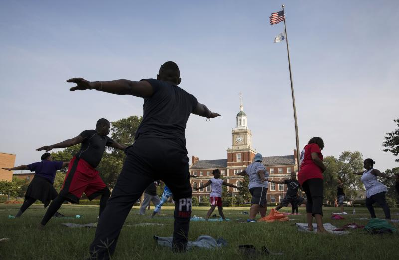 "Participants stretch during a ""yoga on the yard"" class, one of Howard University's sesquicentennial celebration events that was open to anyone who wanted to attend in Washington, D.C. The university is trying to foster better communication with the surrou"