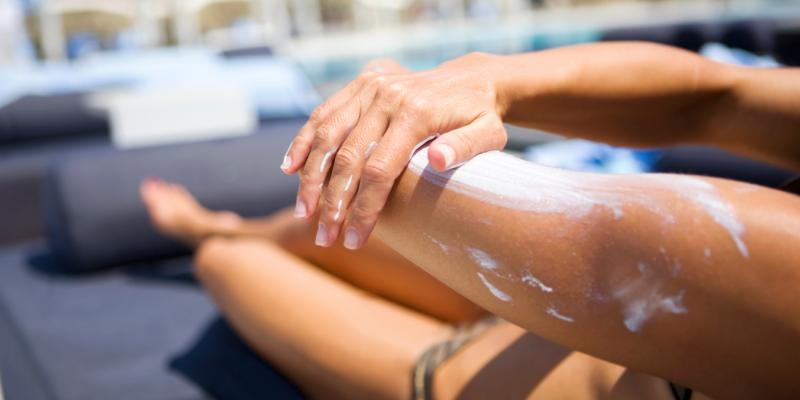 A woman applies sunscreen at the pool.