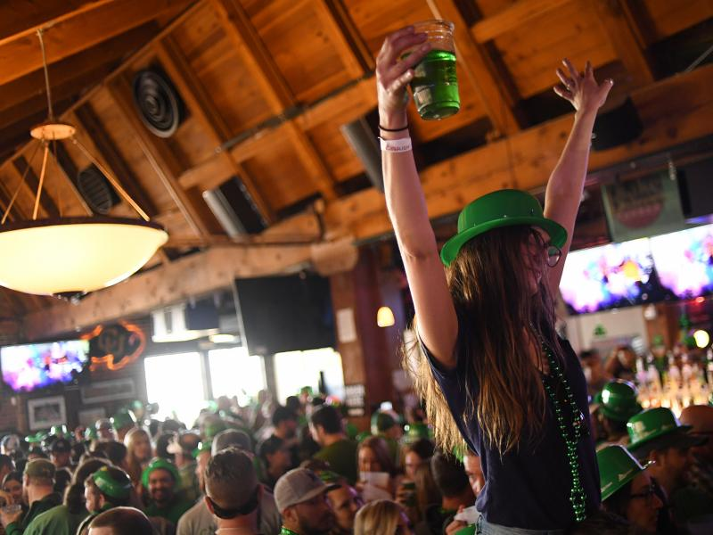A woman dances while sitting on her friend's shoulders during St. Patrick's Day festivities in Denver last year.