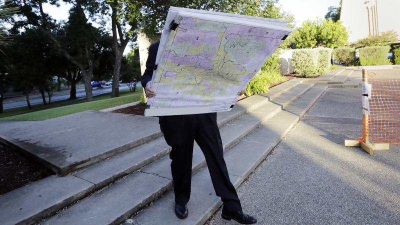 A man with a set of maps heads to a federal courthouse in San Antonio last year for a redistricting trial. Texas is one of three states with cases before the Supreme Court in redistricting.