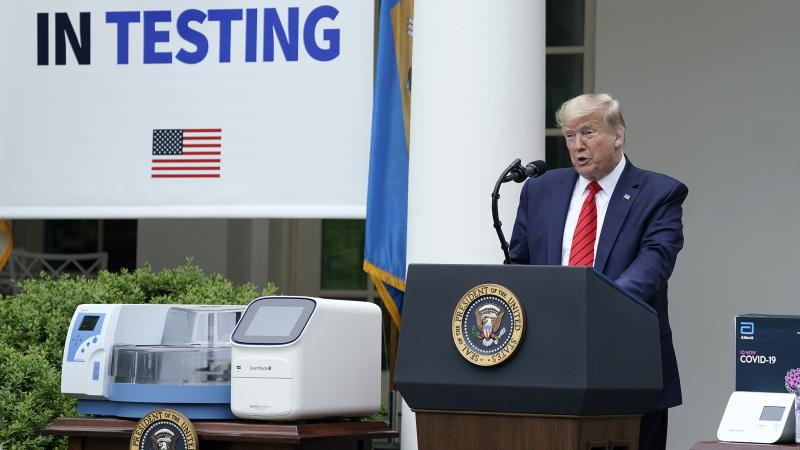 President Donald Trump, flanked by tables holding testing supplies and machines, speaks during a press briefing about coronavirus testing in the Rose Garden of the White House on May 11, 2020 in Washington, D.C.