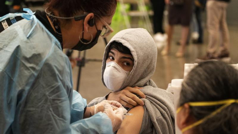 A student looks back at his mother, as he is vaccinated at a school-based COVID-19 vaccination clinic for students 12 and older in San Pedro, Calif., last month.