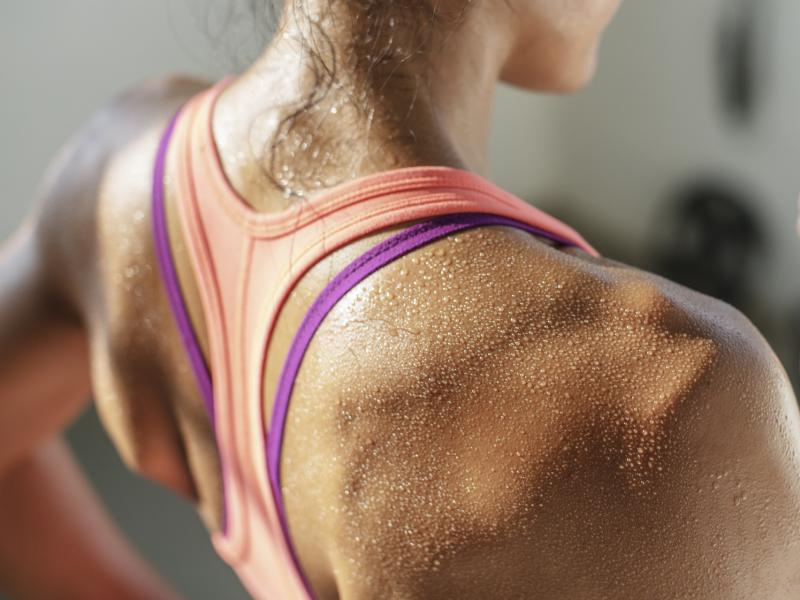 A woman sweats while working out.