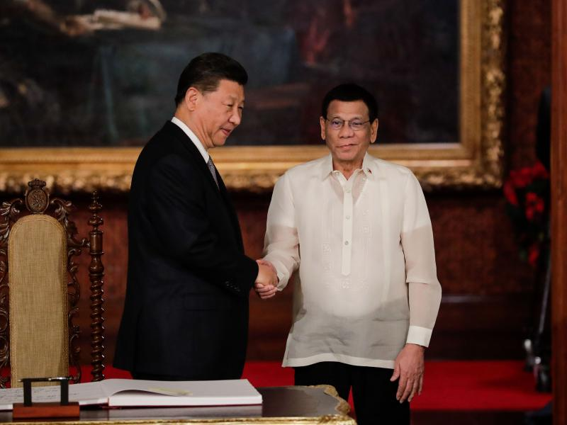"""Chinese President Xi Jinping (left) shakes hands with Philippine President Rodrigo Duterte after a guest book signing at the Malacañang presidential palace in Manila on Tuesday. Duterte called Xi's visit to longtime U.S. ally the Philippines a """"milestone"""