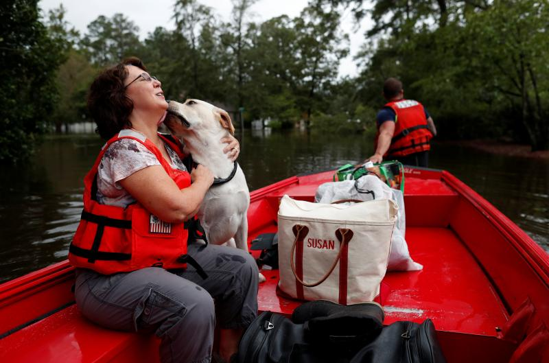 Susan Hedgpeth hugs her dog Cooper Sunday as they go to higher ground via the U.S. Coast Guard in Lumberton, N.C.