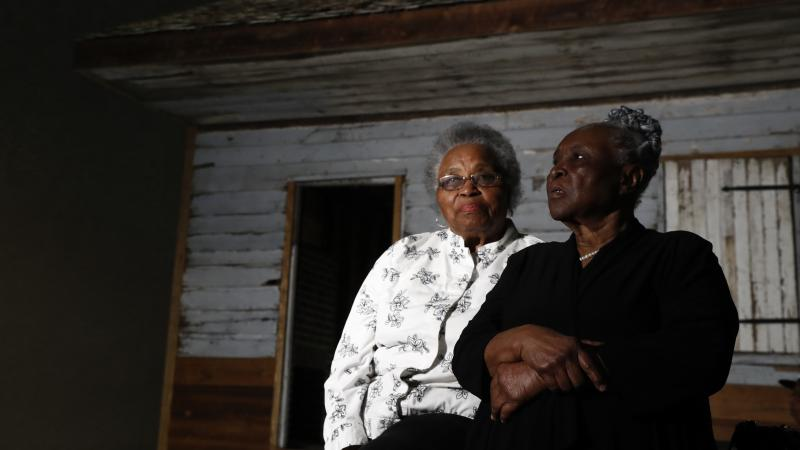 Emily Meggett (left) and Isabell Meggett Lucas sit together at the National Museum of African American History and Culture in front of a slave cabin on display that they grew up in.
