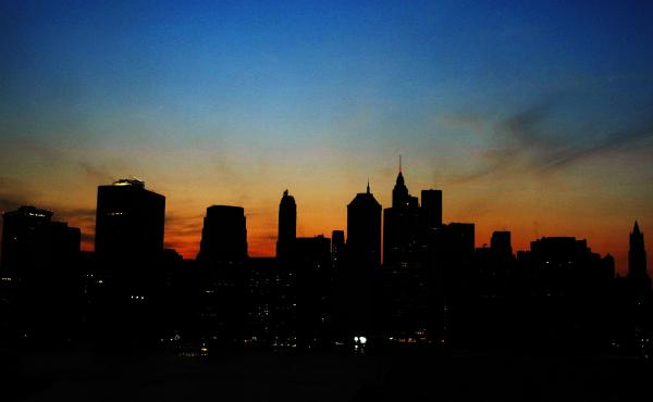 The sun sets over the Manhattan skyline during a major power outage affecting a large part of the Northeastern United States and Canada on Aug. 14, 2003. Ten years later, some improvements have been made to the grid to prevent another large-scale blackout