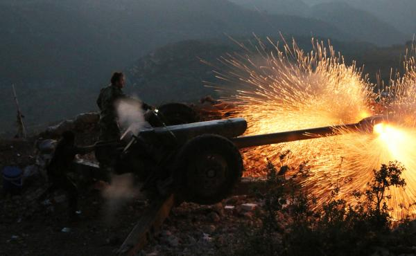 Syrian army personnel fire a cannon in Latakia province, close to the Turkish border in Syria.