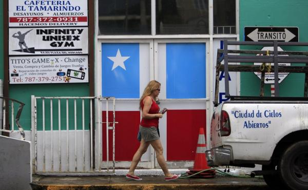 A woman walks in front of a business with the municipal flag painted on the entrance doors in Lares, Puerto Rico, on Sept. 2, 2015. Puerto Rico's economy has been struggling, and Puerto Ricans living on the U.S. mainland, who can vote, vow to be heard thi
