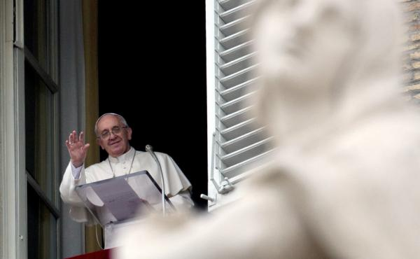 Pope Francis waves to faithful during the Angelus prayer from his studio overlooking St. Peter's Square at the Vatican on Sunday. President Obama will meet with the pope for the first time in March.