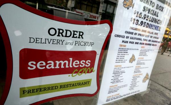 A Seamless sticker is displayed next to the menu in the window of a restaurant in New York's Times Square on Saturday. Rivals Seamless and GrubHub said Friday that they have completed their combination, creating an online takeout company covering about 25