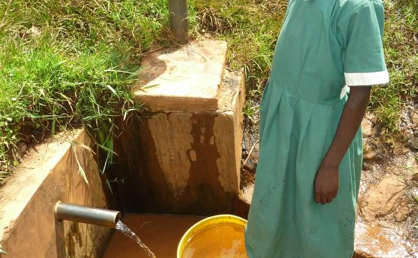 Rodan Gatia gets water from a spring. A chlorine dispenser is behind her.
