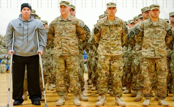 As part of homecoming ceremonies at Joint Base Lewis-McChord in Washington state in January, Army Spc. Tyler Jeffries — with crutches and prosthetic legs — joins his unit in formation as the national anthem is played. The homecoming marked the first t