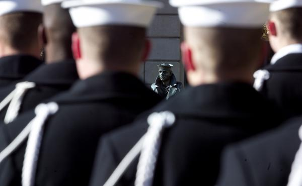 U.S. Navy sailors form a ceremonial guard at a wreath-laying ceremony to memorialize the victims of the attack on Pearl Harbor and pay tribute to the veterans of World War II in front of the Lone Sailor statue at the Naval Memorial in Washington, D.C., in