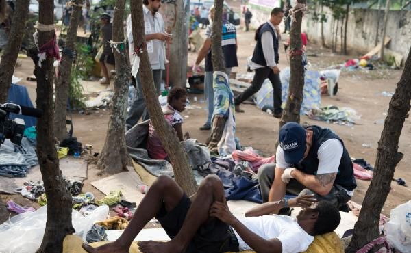 """A member of Rio de Janeiro's Social Work Department speaks with crack addicts in  a slum area known as """"Crackland,"""" during a police operation in the city in November."""