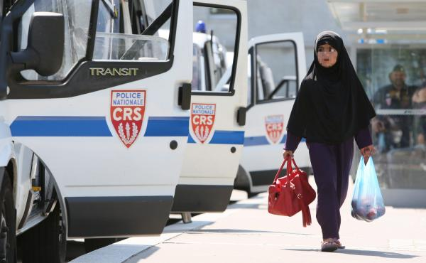 A Muslim woman walks in a Paris suburb where protesters clashed with police over the weekend. The demonstrators oppose the way the police have enforced a ban on Islamic face veils. Five people were injured and six detained in the unrest.