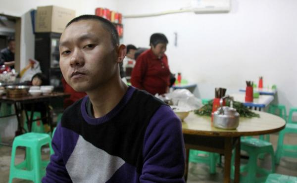 """Ren Jianyu poses for a photograph at a restaurant in Chongqing, China, on Nov. 19, 2012, after being freed from a labor camp. The village official was sentenced to a """"re-education through labor"""" camp after he criticized the government."""