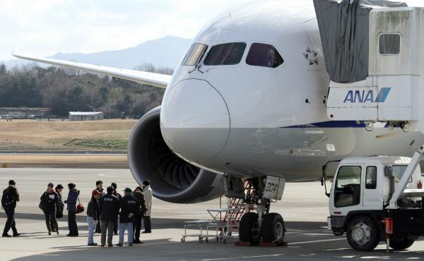 National Transportation Safety Board investigators inspect a Boeing 787 Dreamliner at Japan's Takamatsu Airport. A Federal Aviation Administration investigation into the plane's troubles has widened into a review of the agency's certification process for