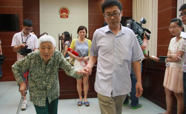 A woman surnamed Chu (left), 77, attends the hearing of a case against her daughter and husband in Wuxi, east China's Jiangsu province, on July 1. Chu's daughter has been ordered to visit her at least once every two months, in the first case under a new l