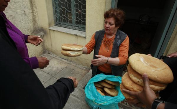 Georgia Kolia, 63, has two adult children, both unemployed. She works as a volunteer distributing loaves of bread at the Agia Zonis Orthodox church soup kitchen for the poor in Athens, Greece, in April 2012.