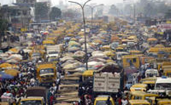 People walk struggling for space between public transport buses and trucks at the burstling Oshodi bus stop in Lagos 06 February 2006. Lagos is reputed as one of the mostly densely populated city in the world with population more than 14 million. AFP PHOT