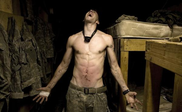 "Spc. Tad Donoho exhibits a ""pink belly,"" in which soldiers hit a colleague's stomach until it bruises for his birthday. ""[Photographer Tim Hetherington] had this tremendous interest in human beings,"" Sebastian Junger tells NPR's Renee Montagne. ""In some w"