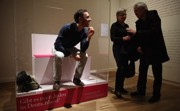 """Bill Glucroft, an American Jew living in Berlin, chats with visitors from his box in the most controversial portion of the Berlin Jewish Museum's exhibition """"The Whole Truth."""""""