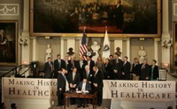 Then-Gov. Mitt Romney signs the Massachusetts health care bill in Boston on April 12, 2006.