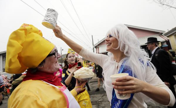 Jill Pasquarella (right) pours powdered sugar on Brandon Connelly, who dressed as a baker from Hubig's Pies, during Mardi Gras in New Orleans in February.