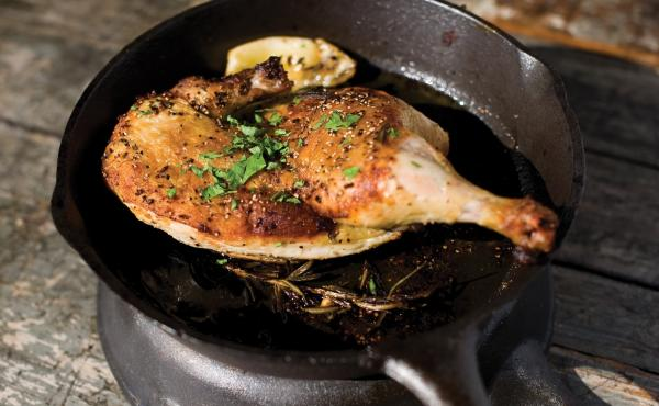 Jay Bentley's technique for Cast Iron Roasted Half Chicken involves cooking a whole chicken between two very hot and heavy pans.