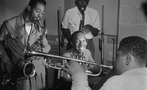 Tadd Dameron (smiling at center) was an important figure in American jazz and bebop. He is shown here with Fats Navarro on trumpet, and Charlie Rouse and Ernie Henry on saxophone.