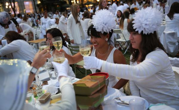 """At Diner en Blanc (""""Dinner in White""""), people arrive dressed all in white. They bring their own food and, fittingly,"""" white wine."""