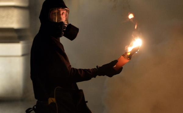 A protester holds a petrol bomb during clashes with riot police after a demonstration against new austerity measures outside the parliament in Athens, Greece, on Nov. 7.