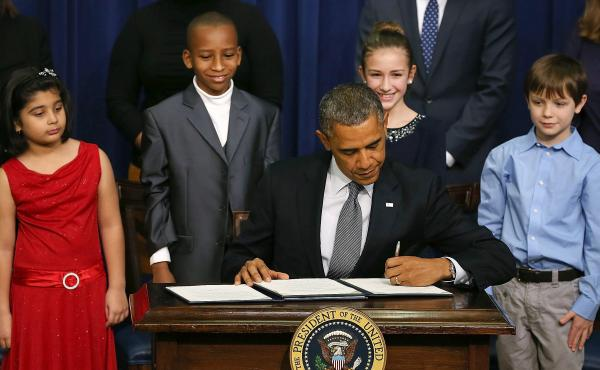 President Obama signs a series of executive orders on gun control Jan. 16 surrounded by children who wrote letters to the White House about gun violence. They are, from left, Hinna Zeejah, Taejah Goode, Julia Stokes and Grant Fritz.