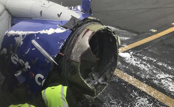 The engine on a Southwest Airlines plane is inspected as it sits on the runway at the Philadelphia International Airport after making an emergency landing there on Tuesday.