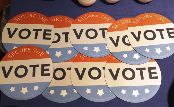 """Computer mouse pads with """"Secure the Vote"""" logos on them sit on a vendor's table at an election officials conference in 2018."""