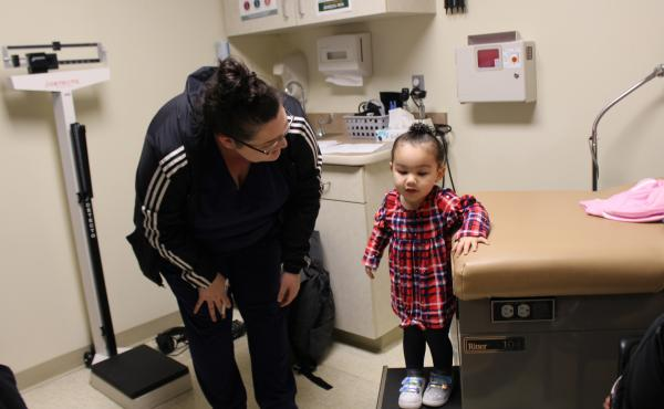 Eliza Oliver helps her daughter, Taelyn, step down from the exam table after a wellness check at the Community Health Center of Southeast Kansas in Fort Scott, Kan. The child's doctor now has a medical scribe to takes notes. The visit this time seemed mor