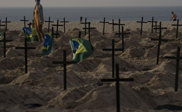 A woman walks amid symbolic graves on Copacabana Beach, dug by activists from the NGO Rio de Paz protesting the government's handling of the COVID-19 pandemic in Rio de Janeiro, Brazil, Thursday.