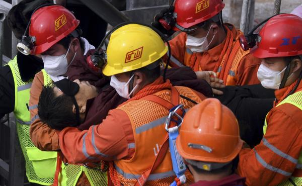 Rescuers carry a worker who was trapped in a gold mine to an ambulance in the city of Qixia in China's Shandong province. Eleven workers trapped for two weeks by an explosion inside the mine were brought safely to the surface on Sunday.