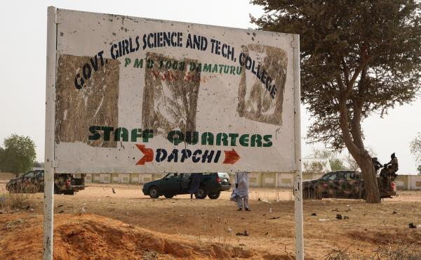 Soldiers drive past a sign leading to the Government Girls Science and Technical College staff quarters in Dapchi, Nigeria, on Thursday. Scores of schoolgirls have been reported missing in Monday's suspected Boko Haram attack.