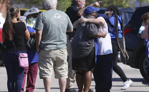 People embrace as police respond to the scene of a shooting at a Kroger grocery store in Collierville, Tenn., on Thursday. Police say 13 people were injured, one of whom has died. The suspected shooter also died from what police say was a self-inflicted g