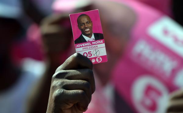 A protester holds a photo of presidential candidate Jovenel Moise near the headquarters of the Provisional Electoral Council in Port-au-Prince last April, as demonstrators demanded that elections be held. Haiti's tortuous election process dragged on for m