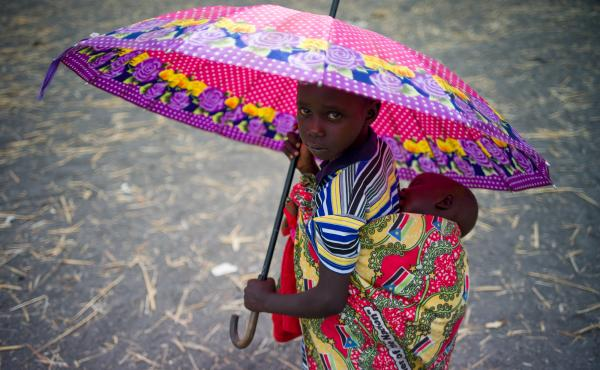 A child holds an umbrella as refugees at a refugee camp in Palorinya, Uganda.