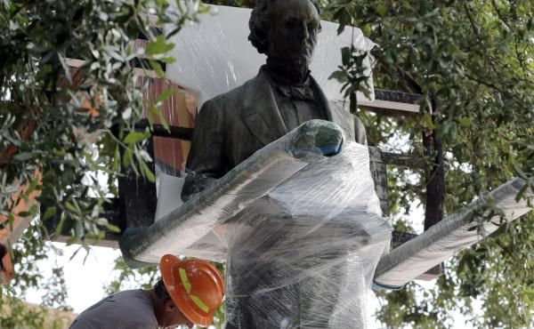 Workers wrap protective materials around a statue of Confederate President Jefferson Davis as they prepare to move the sculpture on the University of Texas campus in Austin, on Sunday.