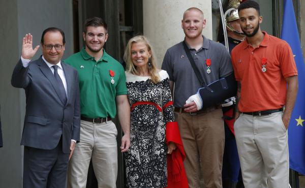 French President Francois Hollande and U.S. Ambassador to France Jane D. Hartley stand with (from left) Alek Skarlatos, Spencer Stone and Anthony Sadler as they leave the Elysee Palace in Paris. The three American men, along with a British citizen, were p