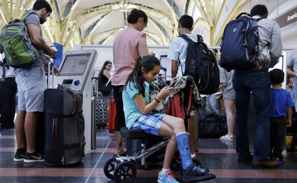 Alisha Lalani, 10, of Ft. Lauderdale, Fla., looks at her phone as her mother and brother check in for their flight to Miami at Washington's Reagan National Airport. Their flight was one of thousands delayed as a result of a technical glitch with an FAA au
