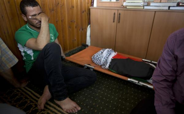 A Palestinian man mourns alongside the body of a one-and-a-half year old boy, Ali Dawabsheh, during his funeral in Duma village near the West Bank city of Nablus on Friday.