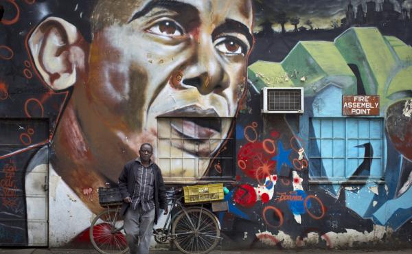 A man in Nairobi, Kenya, stands in front of a mural of President Obama, created by the Kenyan graffiti artist Bankslave, ahead of Obama's trip to Kenya and Ethiopia.
