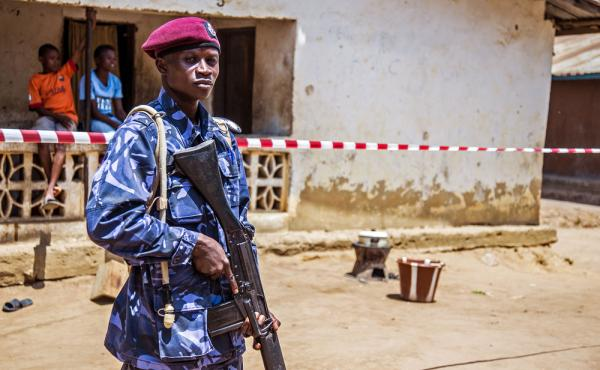 A police officer guards the home of a family under a 21-day Ebola quarantine in Freetown, Sierra Leone, back in March.